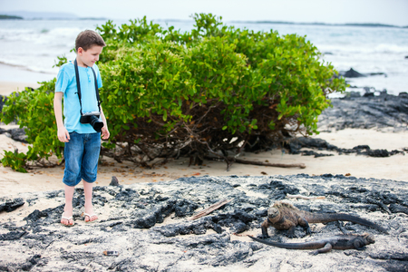 Little boy at beach with volcanic lava rock formations on Galapagos islands