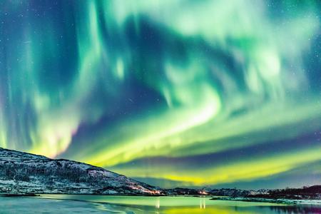 Increíble actividad de auroras boreales Aurora Boreal sobre la costa en Noruega