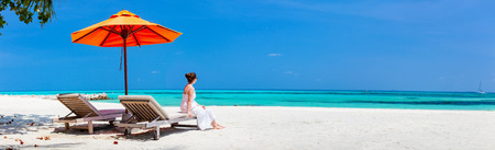 Panorama of young beautiful woman relaxing at tropical beach during summer vacation