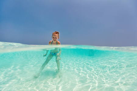 Split underwater and above photo of a little girl splashing in tropical ocean