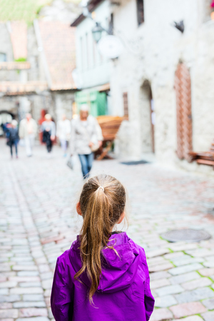 Back view of adorable girl outdoors exploring Tallinn old town 版權商用圖片