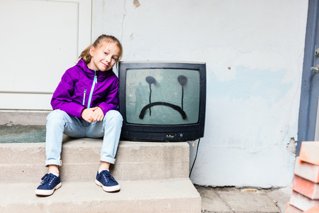 Adorable girl sitting next to vintage TV with sad face drawn on it