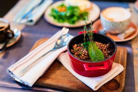 Buckwheat porridge in red casserole served in restaurant for lunch or dinner Stock Photo