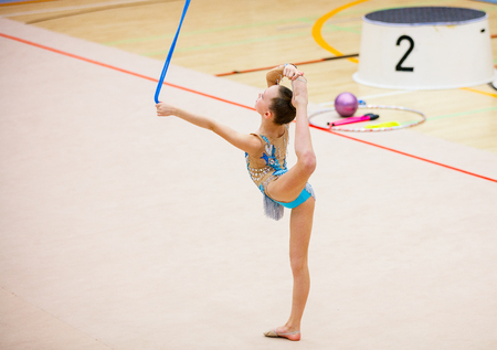 Adorable girl with rope competing in rhythmic gymnastics