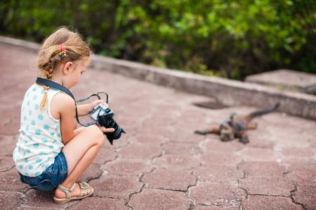 Adorable little girl photographing marine iguana 스톡 콘텐츠