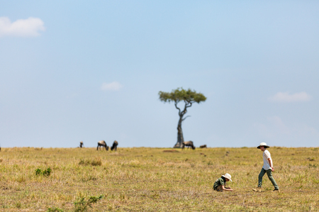 Kids witnessing great migration of wildebeests in Masai Mara National park in Kenya