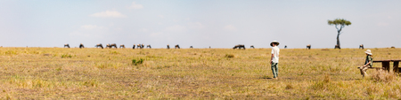 Panorama of kids witnessing great migration of wildebeests in Masai Mara National park in Kenya