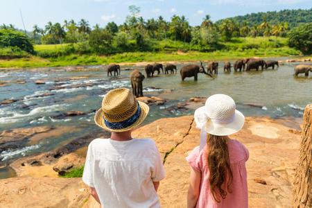 Kids watching Sri Lankan elephants at riverbed drinking water