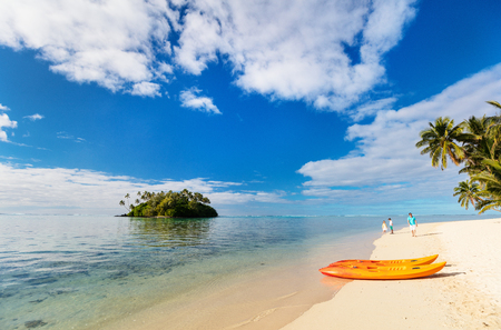 Two kayaks at beautiful tropical beach with palm trees, white sand, turquoise ocean water and blue sky at Cook Islands, South Pacific