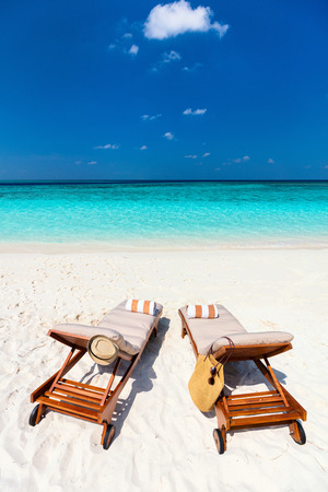 Wooden lounge chairs on a beautiful tropical beach at Maldives Stock Photo
