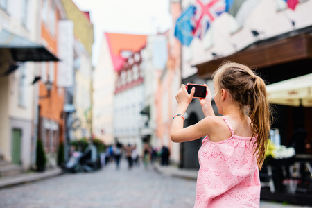 Back view of adorable girl outdoors exploring Tallinn old town on summer day