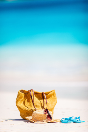 Straw bag, sun glasses, towel and flip flops on a tropical beach Stock Photo