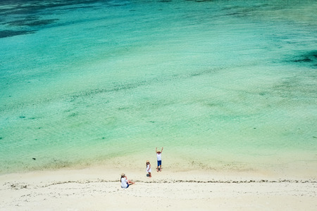 Aerial view of a tropical coast with mother and kids enjoying beach vacation