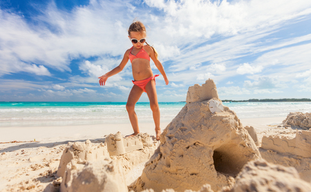 Little girl at tropical beach making sand castle