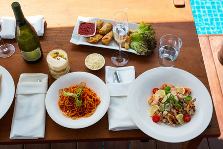 Top view of delicious spaghetti bolognese and shrimp salad served for lunch at luxury resort or restaurant Stock Photo