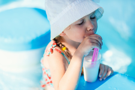 Cute little girl at all inclusive resort swimming pool sipping cocktail