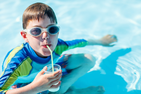 Cute boy at all inclusive resort swimming pool sipping cocktail Stok Fotoğraf