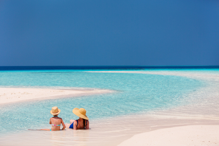 Mother and daughter enjoying tropical beach vacation Stock Photo