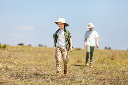 Kids brother and sister on African safari vacation walking in savanna