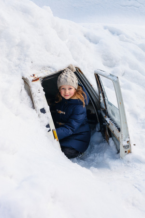 Adorable little girl outdoors on beautiful winter day in a car cover with snow after heavy snowfall Banco de Imagens