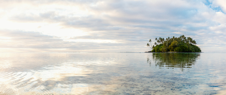 Beautiful tropical island with palm trees surrounded by turquoise ocean water during sunrise or sunset at Cook Islands, South Pacific