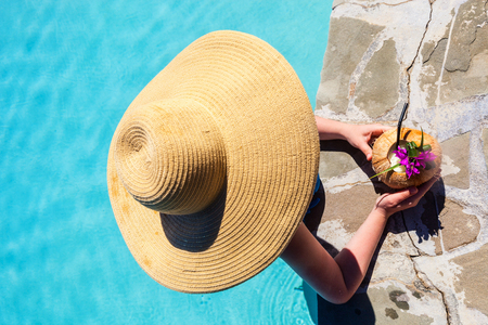Top view of girl relaxing in swimming pool with tropical drink Stok Fotoğraf
