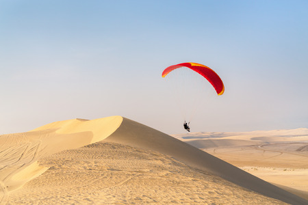 Unrecognizable paraglider flying over sand dunes in Qatar desert