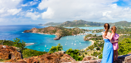 Panorama of family mother and daughter enjoying aerial view of picturesque English Harbour at Antigua and Barbuda in Caribbean Stock Photo