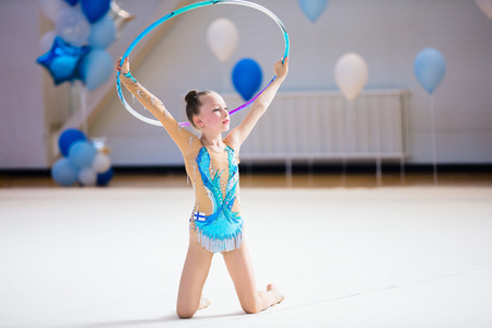 Adorable girl in rhythmic gymnastics competition with hoop