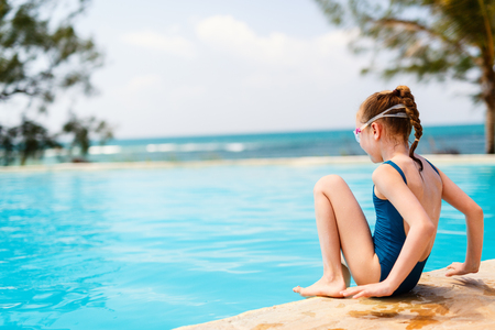 Adorable little girl at swimming pool having fun during summer vacation Stock Photo