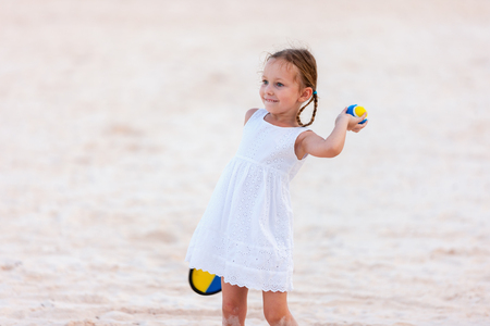 Little girl playing beach tennis on vacation