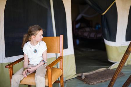 Little girl in safari tent enjoying  luxury vacation in Africa