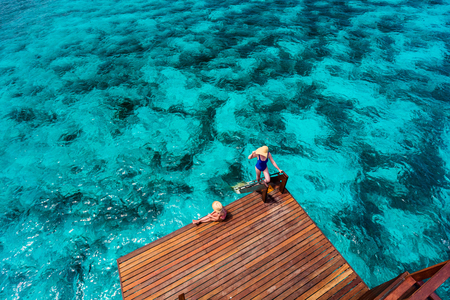Mother and daughter at wooden dock of overwater villa in Maldives Stock Photo