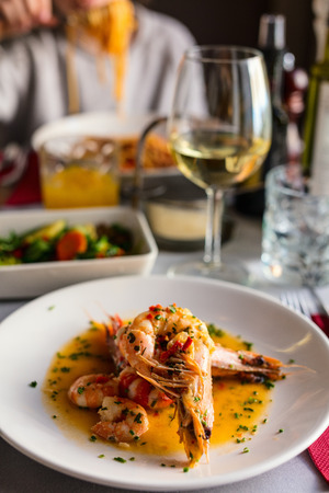 Close up of delicious seafood giant shrimps served with grilled vegetables and white wine for lunch or dinner