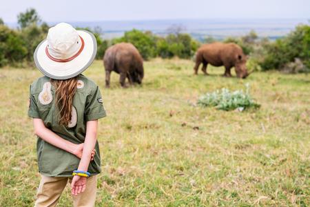Back view of a little girl on safari walking close to  white rhinos Standard-Bild - 104505934