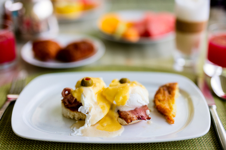 Delicious breakfast with eggs Benedict and coffee