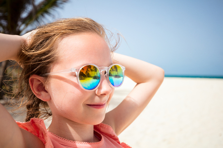 Adorable little girl at beach during summer vacation wearing sunglasses reflecting tropical beach with palm trees Stok Fotoğraf - 107393338