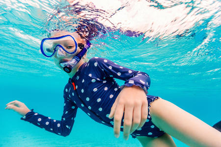 Underwater photo of young girl swimming and snorkeling in tropical ocean Standard-Bild
