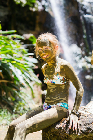 Portrait of cute little girl covered in mud in front of beautiful waterfall traditional tourist activity on St Lucia island in Caribbean