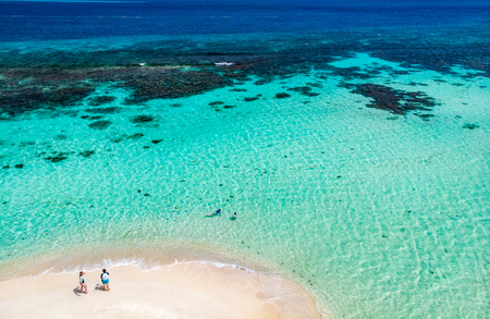 Aerial drone view of tiny tropical Mopion island sandbar, turquoise Caribbean sea and a family with kids in St Vincent and Grenadines