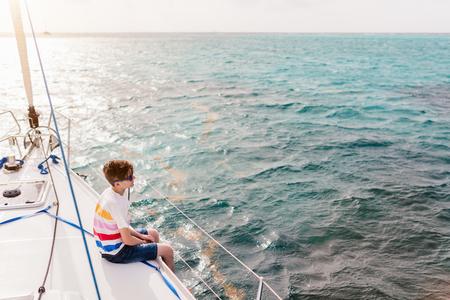 Teenage boy enjoying sailing on board a chartered catamaran or yacht