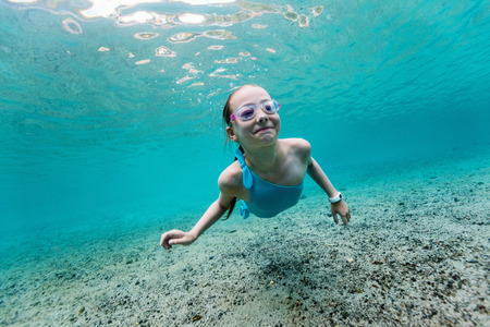 Underwater photo of young girl swimming in tropical ocean