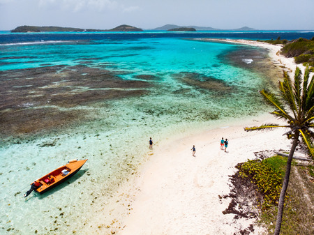 Aerial drone view of Petit Tabac tropical island, turquoise Caribbean sea of Tobago cays, and a family with kids in St Vincent and Grenadines Stock Photo - 107393777