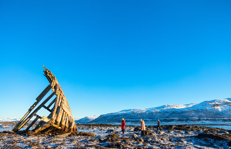 Family of mother and kids exploring shipwrecked wooden viking boat in Northern Norway