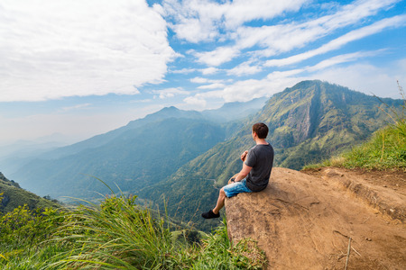 Young man enjoying breathtaking views over mountains and tea plantations from Little Adams peak in Ella Sri Lanka