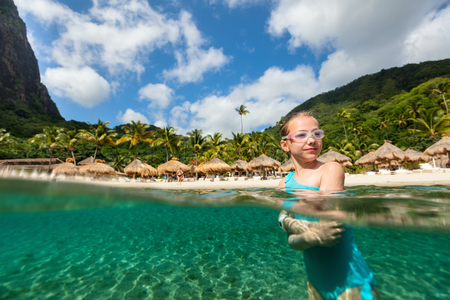 Split underwater photo of a little girl enjoying summer vacation on exotic island in Caribbean