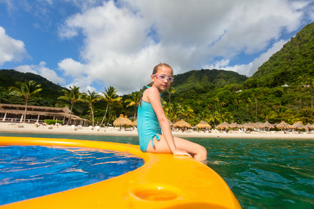 Young beautiful girl enjoying summer vacation on exotic island in Caribbean