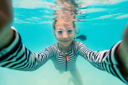 Underwater photo of a little girl swimming in tropical ocean and taking selfie Reklamní fotografie - 108835354