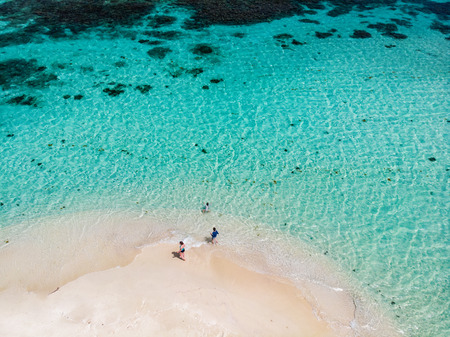 Aerial drone view of tiny tropical Mopion island sandbar, turquoise Caribbean sea and a family with kids in St Vincent and Grenadines Foto de archivo - 108835397