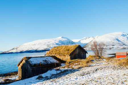Beautiful winter landscape of Northern Norway with wooden huts overlooking breathtaking fjords scenery Stock Photo